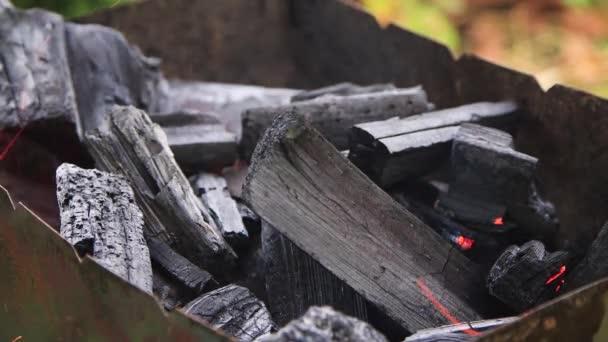 Rozdmýchej oheň na uhlících ležících v grilu.