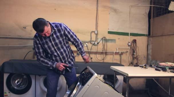 Der Mann montiert das Armaturenbrett der Waschmaschine.