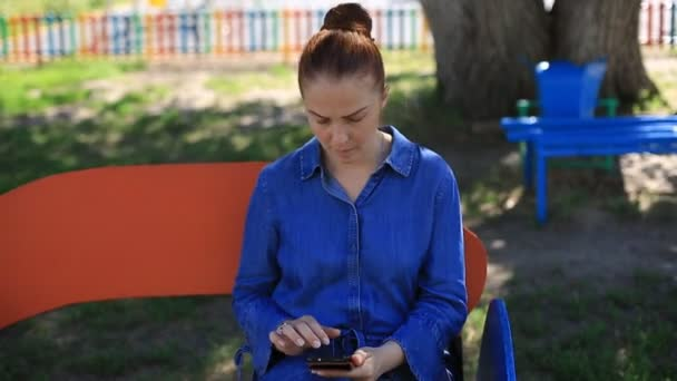 a beautiful young woman with red hair in a denim dress and freckles on her face is sitting in the Park on a bench on a summer day looking at the camera and smiling. close up.