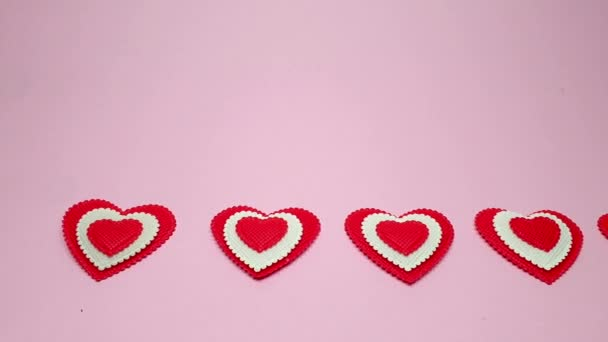 small red hearts on a soft pink colored background, copy space. Valentines Day concept for design