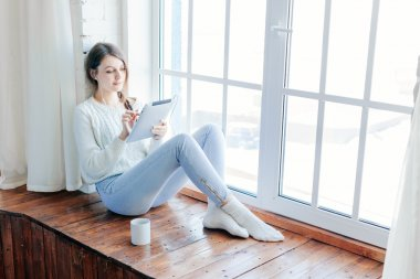 Young beautiful long hair woman using tablet computer indoor.