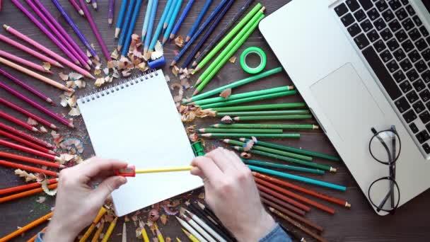 Arbeitsplatz mit Buntstiften, Laptop, Palette auf Holztisch