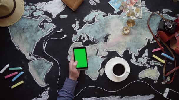Hand, map, compass, money and phone on the chalkboard table.