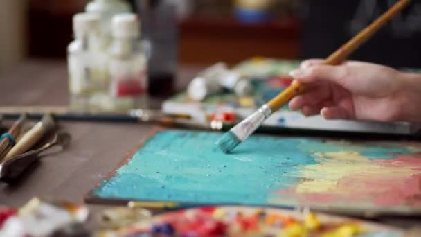 artist paints a picture of oil paint brush in hand with palette closeup.