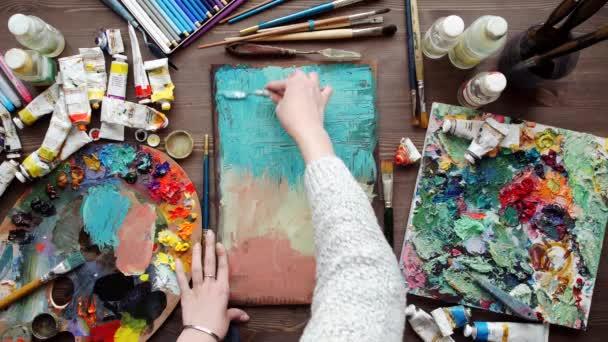 umělec maluje obrázek olejomalba štětec v ruce s paletou detailní up.