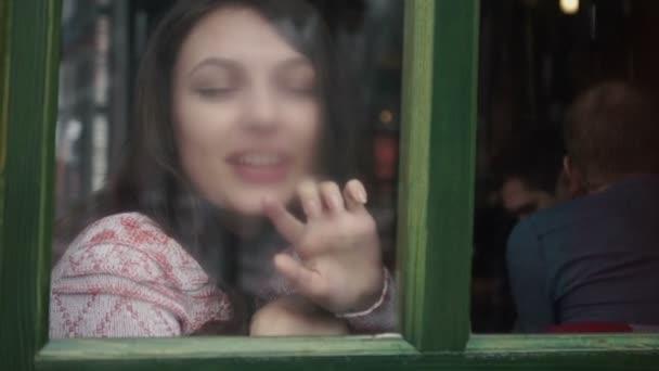 schöne Mädchen auf der Fensterbank sitzen und Malen auf Glas