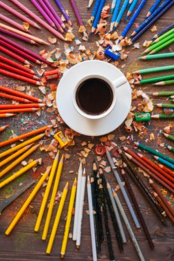 Color pencil and a cup of coffee on wooden background