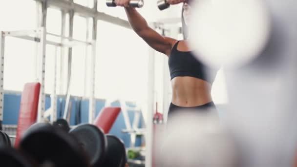 Sportovní fitness žena se svaly s činkami čerpání