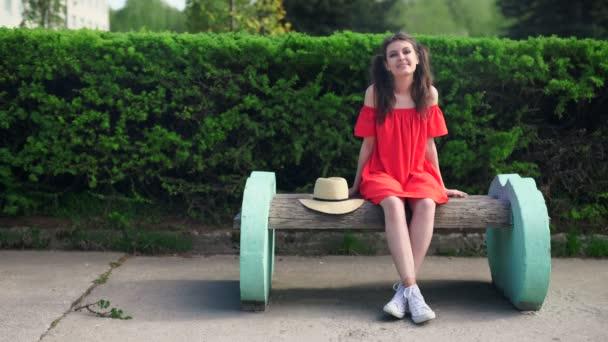 Krásný happy model stojící hravé v červených šatech na přírodu