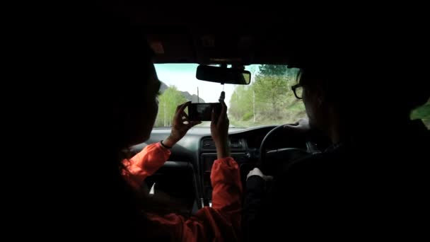 happy man and woman driving in cabriolet car and taking selfie with smartphone