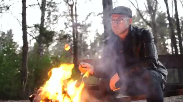 Detailní portrét člověka smažené klobásy na oheň v lese