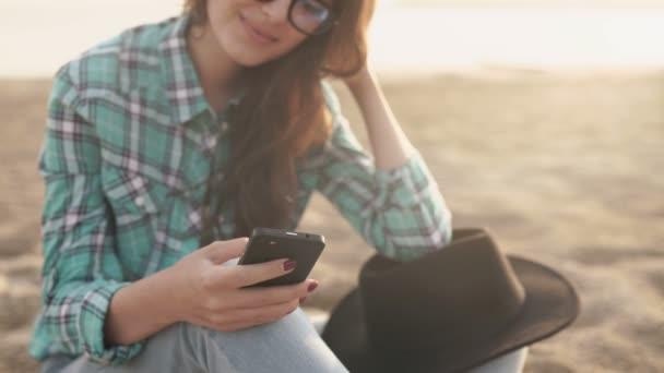 junge stylische hübsche Frau, die Hände halten ein Telefon, Jeanshemd und Jeans