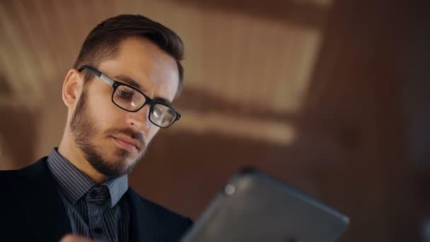 Mladé vousatých podnikatel psaní obchodních e-mailů pomocí počítače tablet pc