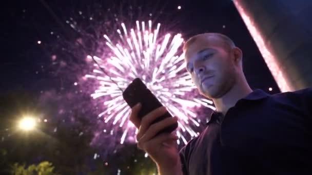člověk využít chytrý telefon, obraz ohňostroj jako pozadí.
