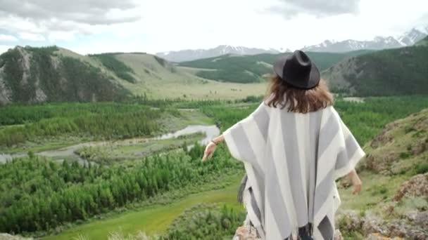 Mladá krásná žena cestující na sobě klobouk a pončo relaxační na vrcholku kopce s hory a kopce kolem
