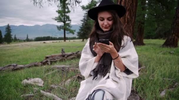 usmívající se žena pomocí mobilního telefonu v parku na podzim
