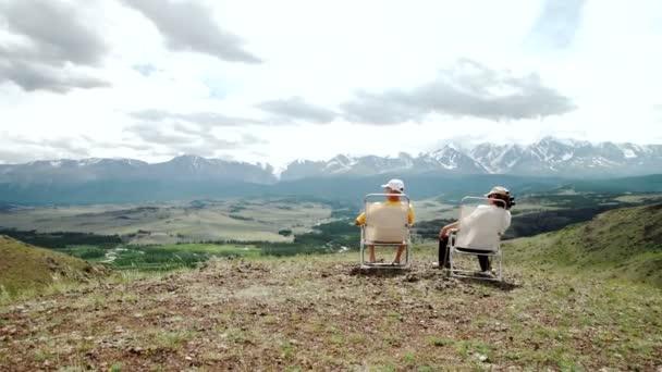 starší pár chůzi držení rukou při západu slunce