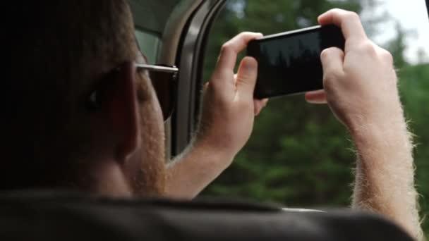 Rückansicht des jungen Paares fahren im Auto und die Fotos von Straße mit smartphone
