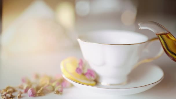 pour tea in a beautiful white cup with lemon and roses