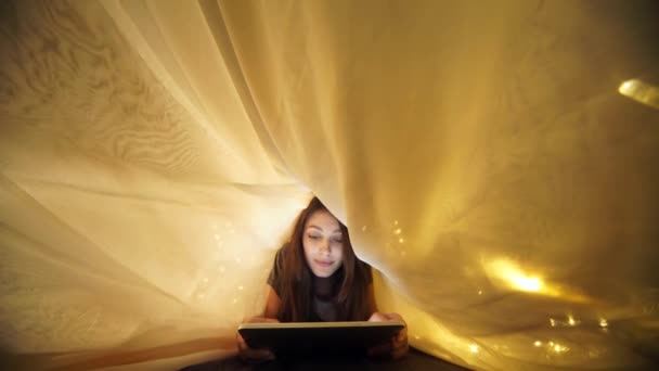 Girl using digital tablet under blanket while lying on bed at home