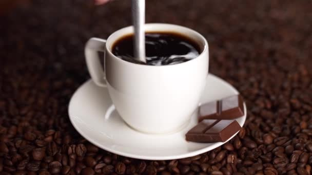 in a white cup of coffee on coffee beans with a spoon prevent sugar