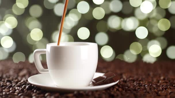 Coffee poured in a white cup on the coffee beans on the background of lights