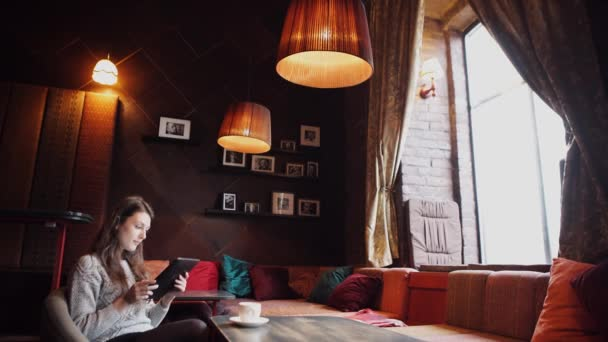 fiatal nő kávét inni, és segítségével tabletta számítógép, egy kávézóban
