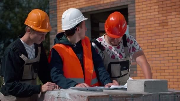 Junge Architekten mit Entwurf diskutieren Skizze des Neubaus