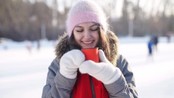 Dívka s hrnek horké nápoje na ledové kluziště