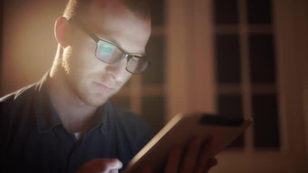 ember, dolgozik este fekve kanapé a nappaliban, tabletta