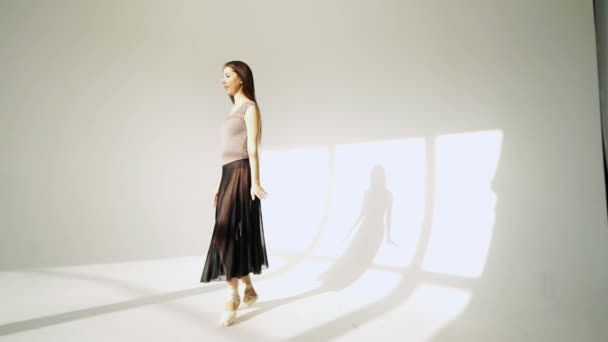 silhouette of ballerina in classical tutu in the white studio.