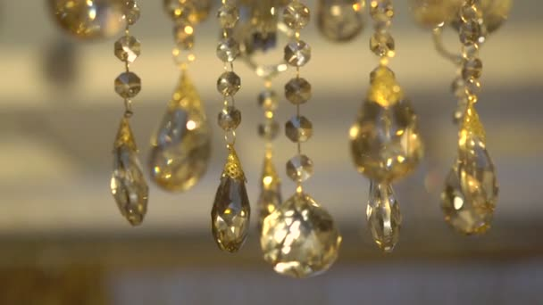 Moving of a bright crystal chandelier on a dark background. Slowly