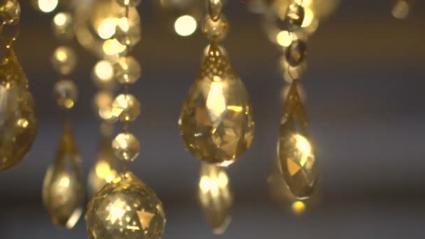 Luxury crystals of a classic chandelier on a dark background. Slow motion