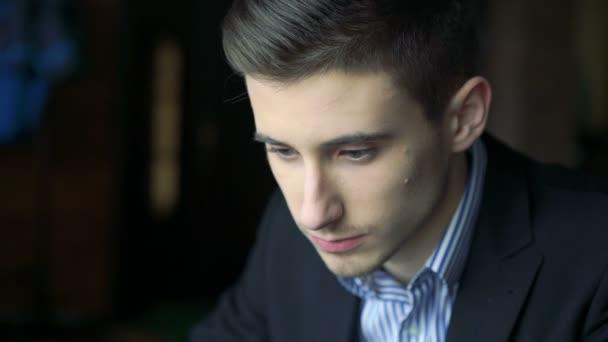 Pohledný mladík přihlížel a myšlení v kavárně