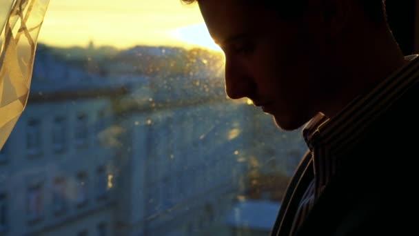 Portrait of man using phone near the window with sun shining. Zoom