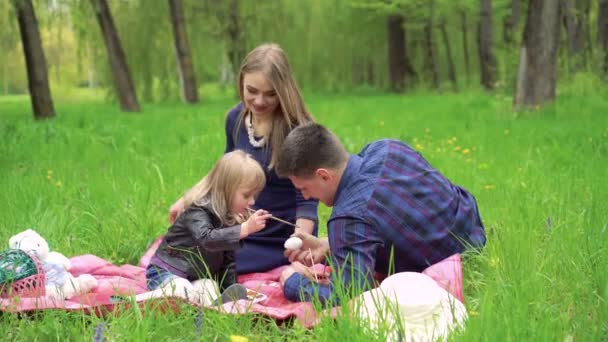 Young family with baby painting Easter eggs on a parks grass. 4k