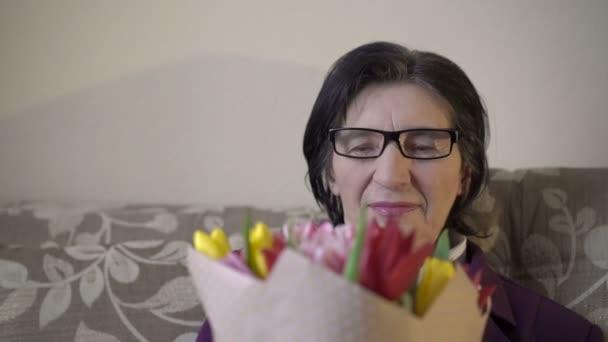 Stará žena v brýlích držení kytice tulipánů, vonící, s úsměvem