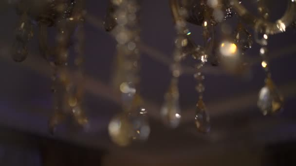 Bright brilliant chandeliers parts on the background. Slowly