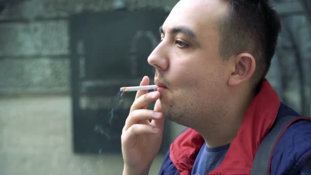 Close up of a man looking on camera and smoking a cigarette on the street 4k