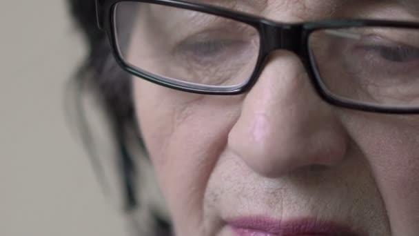 Closeup část starých ženách tvář: hlavou, rty, nos, oči při pohledu dolů, brýle