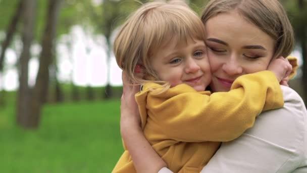 Malá holčička objímat matku a políbil ji v parku. Pomalu