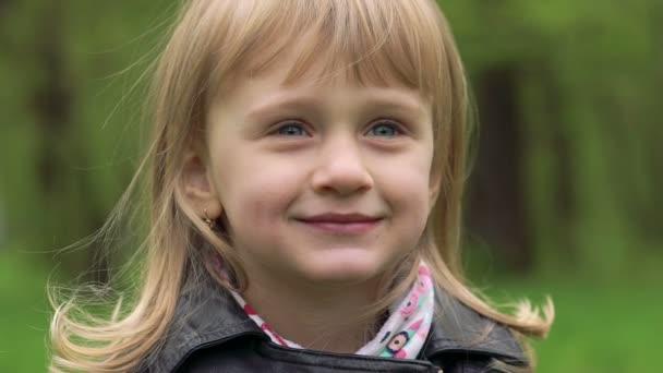 Portrét, 3 roky stará dívka s úsměvem na fotoaparátu. Pomalu