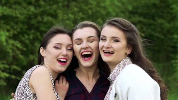 Zblízka tří dívek v objetí, usmíval se a při pohledu na fotoaparát. Pomalu