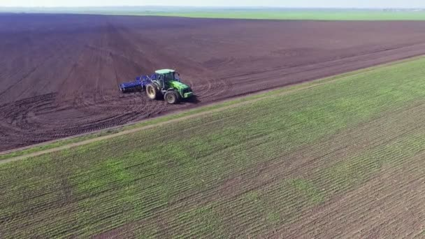 Aerial view of tractor turning around and plowing the soil.