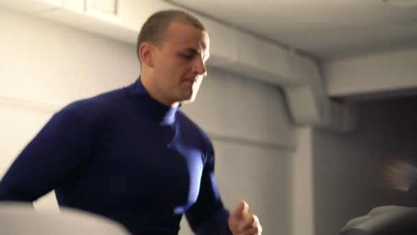 Strong boy running on a racetrack in a gym in 4k