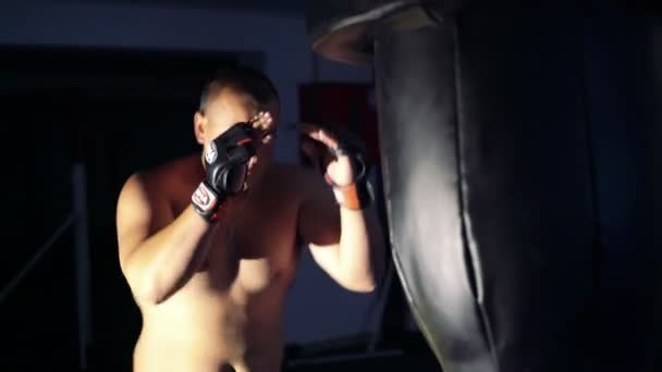 Strong man doing exercise with punching bag in the dark gym. 4k