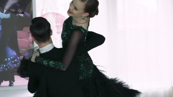 Young couple performs scrolling in ballroom dancing