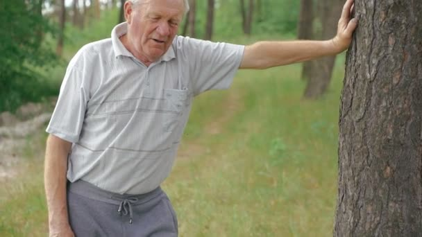 Old man resting near the tree after exercises, breathing