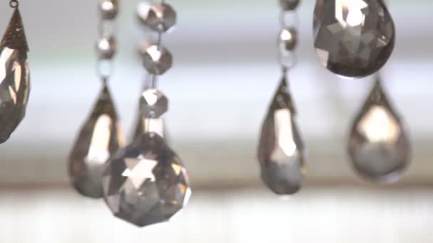 Luxury crystals of a classic chandelier on a light background. Slow motion