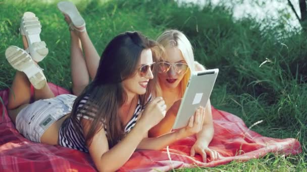 Pretty carefree girls lying on blankets on the grass and using the tablet. 4k